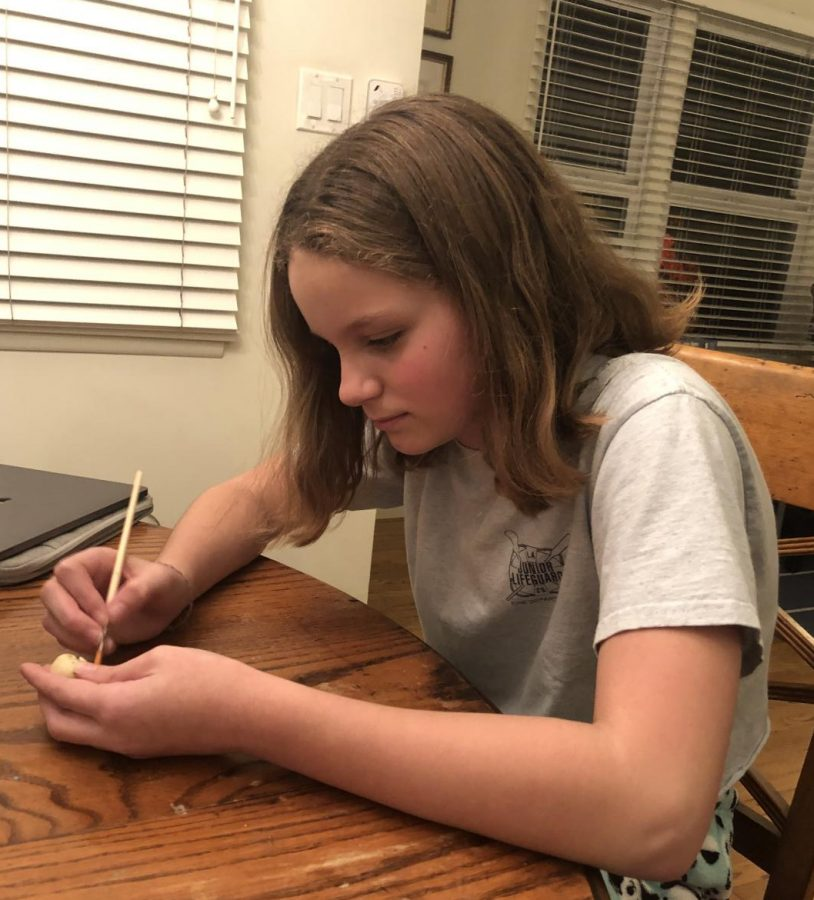Landry is sitting here working on a sculpture for art class. She loves art and is very passionate about it.